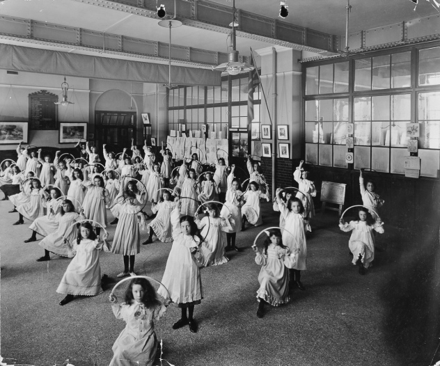 Girls with hoops, Lavender Hill Girls School, Bermondsey, London, 1906. Girls performing an exercise drill involving the use of hoops in the school hall. Artist: unknown. (Photo by City of London: London Metropolitan Archives/Heritage Images/Getty Images)